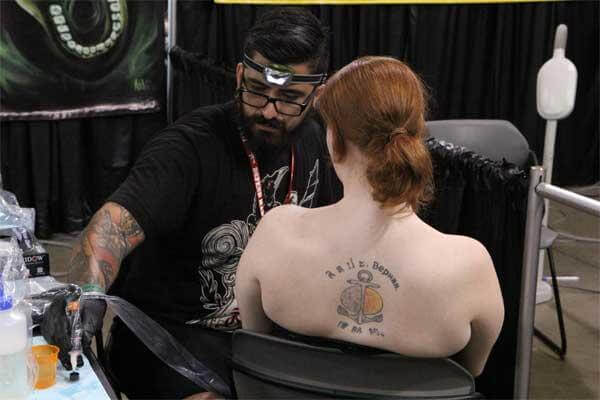 A member of the U.S. Navy sits for a tattoo with one of the many renowned tattoo artists who travel annually to the Pacific Ink & Art Expo, Blaisdell Exhibition Hall, Honolulu, Hawaii, Aug. 3, 2013. (U.S. Air Force photo by Tech. Sgt. Phyllis Keith)