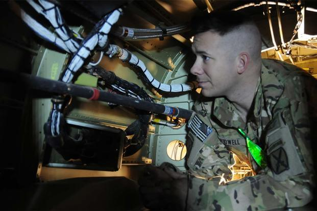 U.S. Army Sgt. Justin Bridwell, an avionics mechanic, demonstrates the limited space inside the tail boom of a UH-60M Black Hawk helicopter. (U.S. Army photo by Staff Sgt. Todd Pouliot)