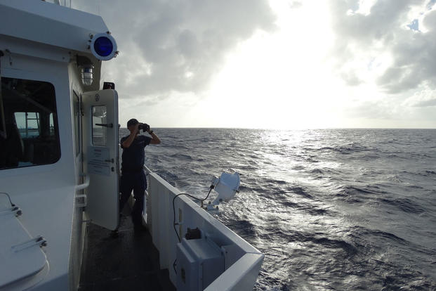 A crewmember aboard the Coast Guard Cutter Heriberto Hernandez is on the lookout for possible survivors of a migrant capsized vessel in waters between the British Virgin Islands and St. Maarten July 14, 2016. (Photo: U.S. Coast Guard)