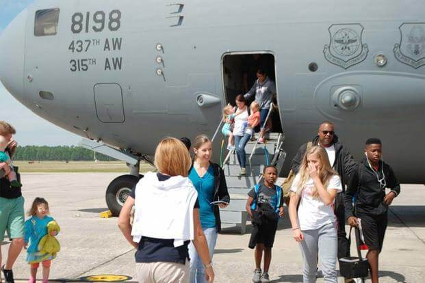 Some of the approximately 700 family members eventually to arrive at NAS Pensacola as part of Hurricane Matthew evacuation from Naval Station Guantanamo Bay depart their aircraft. (U.S. Navy photo by Cathy Whitney)