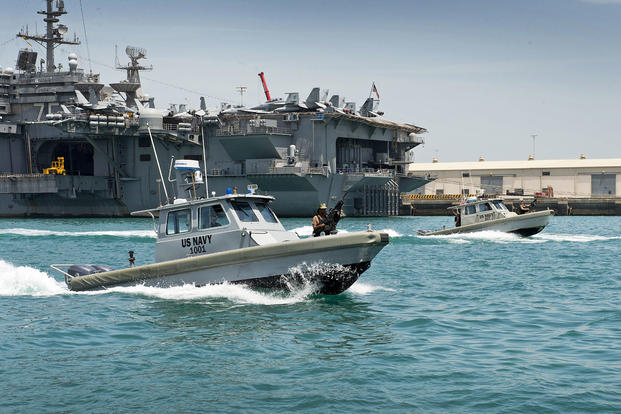 Sailors assigned to the harbor patrol unit at Naval Support Activity Bahrain maneuver harbor patrol craft in formation past the aircraft carrier USS Harry S. Truman. (Mass Communication Specialist 1st Class Gary Granger Jr./Navy)