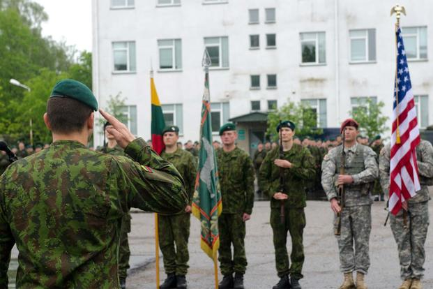 FILE -- Lithuanian army Maj. Gen. Almantas Leika renders honors to Lithuanian and American flags during a ceremony to open Exercise Black Arrow 14 in Rukla, Lithuania, May 12, 2014. (US Army/ Sgt. A.M. LaVey)