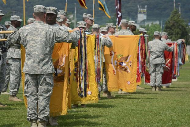 FILE -- Commanders of the 2nd Armored Brigade Combat Team, 1st Cavalry Division, uncase their unit's colors for the first time in South Korea during a transfer of authority at Camp Casey, July 13, 2015. (U.S. Army / Staff Sgt. John Healy)