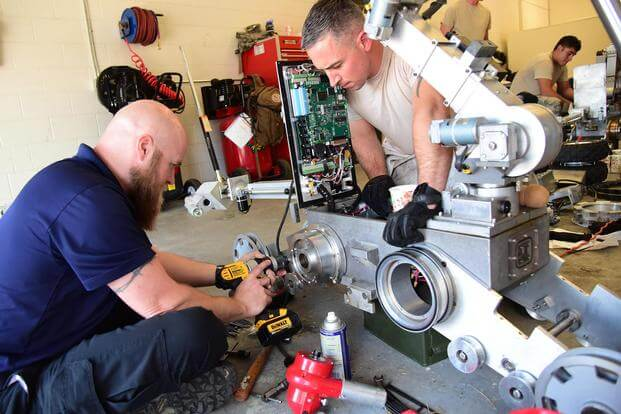 Technical Sgt. Dustin Frey, an EOD technician, assists Jack Caylor, Northrop Grumman Remotec robotic instructor, remove a difficult component during a maintenance class at Peterson Air Force Base, Colo., Aug. 17, 2016. Staff Sgt. Amber Grimm/Air Force