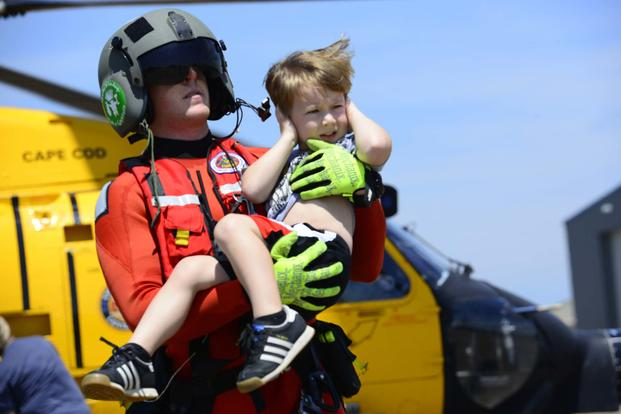 Coast Guard Petty Officer 3rd Class Evan Gallant, a rescue swimmer from Air Station Miami, carries a boy away from an MH-60 Jayhawk helicopter in Beaumont, Texas, Aug. 31, 2017 (U.S. Coast Guard/Petty Officer 3rd Class Corinne Zilnicki)