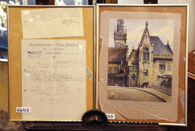 A picture that was probably painted by Adolf Hitler, right, and documents of originality, top lef, and a contract of sale is displayed in a auction house in Nuremberg, Germany.