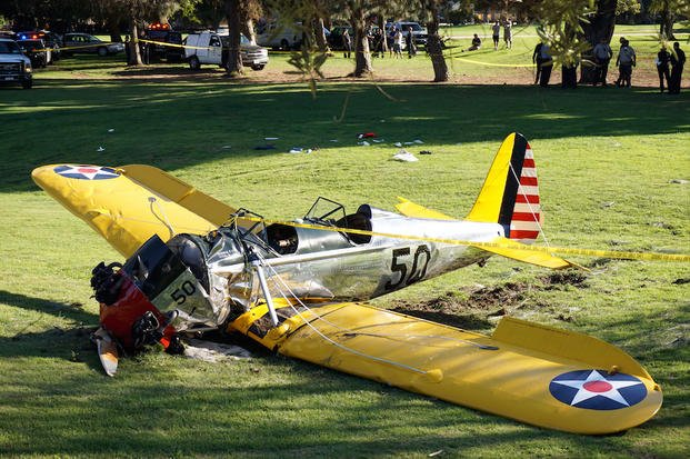 In this Thursday, March 5, 2015 file photo, a  World War II-era trainer airplane rests on the ground after actor Harrison Ford crash-landed it after reporting the engine failed on the Penmar Golf Course in the Venice area of Los Angeles.
