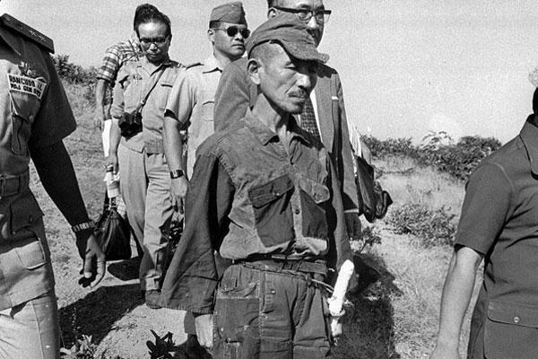 In this 1974 file photo, Hiroo Onoda, wearing his 30-year-old imperial army uniform, cap and sword, heads for a helicopter landing site on Lubang Island for a flight to Manila when he comes out of hiding in the jungle.