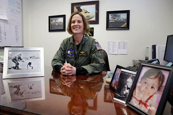 Navy Cmdr. Valerie Overstreet poses in her office on the U.S. Naval Academy campus in Annapolis, Md. At left is a photograph of Overstreet as a child running to her father, Gil Rud, who spent his career as a Navy pilot.