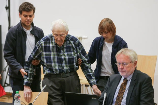 Former Auschwitz guard Oskar Groening, second left, is led into a courtroom in Lueneburg, northern Germany, on July 14, 2015. Axel Heimken/Pool Photo via AP