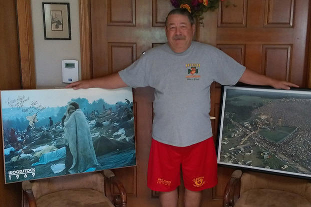"Former Marine Cpl. James ""Corky"" Corcoran, 68, holds up posters of the 1969 Woodstock Music Festival, including the famous Burk Uzzle photo (left), where Corcoran can be seen in the lower right corner. James Corcoran photo, used with permission"