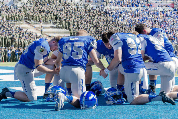 Members of the Air Force Academy's football team pray together before a game; their public religious displays are now being investigated by the academy. (DoD photo)