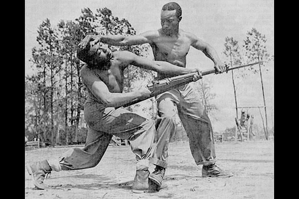 "Cpl. Alvin ""Tony"" Ghazlo, the senior bayonet and unarmed combat instructor at Montford Point, demonstrates a disarming technique on his assistant, Private Ernest ""Judo"" Jones. (U.S. Marine Corps)"