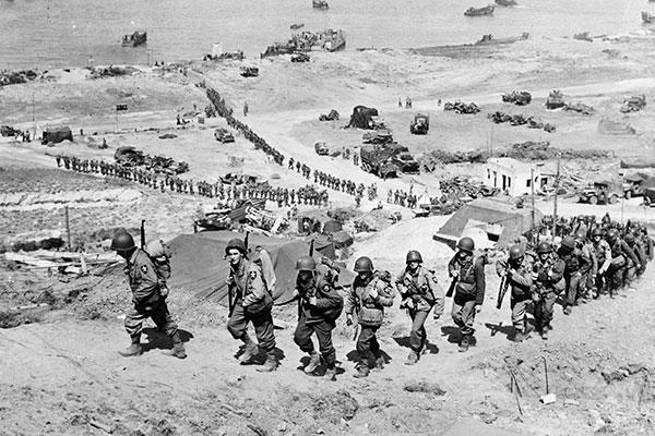 This picture of Omaha Beach at the end of the invasion's first day shows the bluff Gen. Cota's men had to climb under fire. Note the bunker the men are walking past. (National Archives)