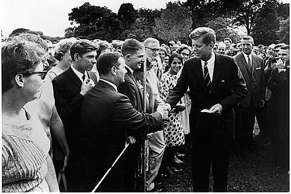President Kennedy greets Peace Corps workers in 1961. Junger argues that mandatory national service with military and non-military options could build a more cohesive society. (White House photo/Abbie Rowe)