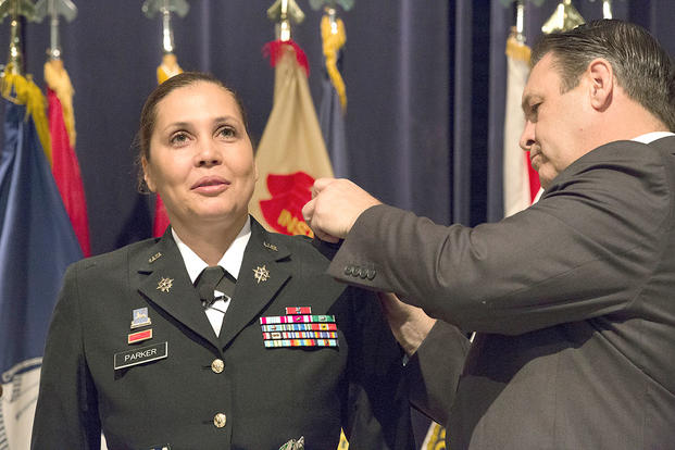 Davis Tindoll Jr., Atlantic Region Director of the U.S. Army Installation Management Command, pins the rank of colonel on the shoulders of Picatinny Arsenal garrison commander, Col. Ingrid Parker. (U.S. Army/Todd Mozes)
