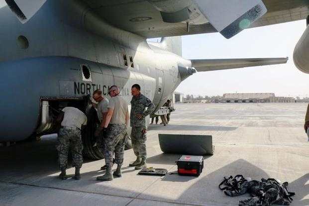 Crew members from the 386th Expeditionary Aircraft Maintenance Squadron inspect a C-130 on a flightline in Iraq after its engines overran in the heat. (Military.com photo by Oriana Pawlyk)