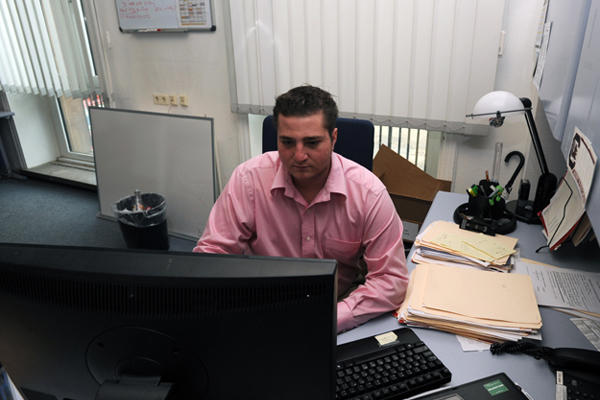 Businessman in a pink shirt using a computer.