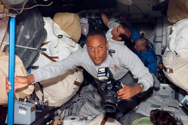 Specialist Alvin Drew Jr. holds a camera in space.