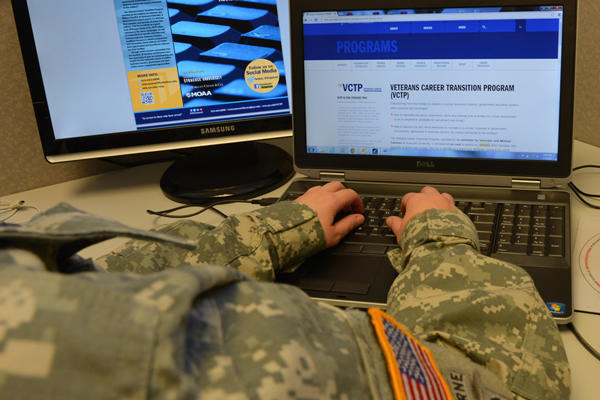 Service member using a computer at a desk.