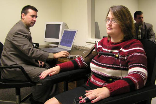 Polygraph test in an office while sitting in a chair.