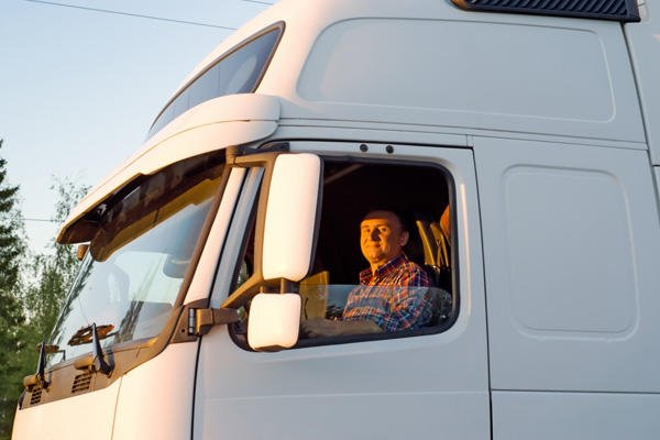 Truck driver in a white cab.