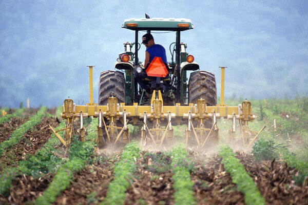 Farmer operating a tractor.