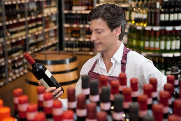 Sales clerk holding wine bottle in shop