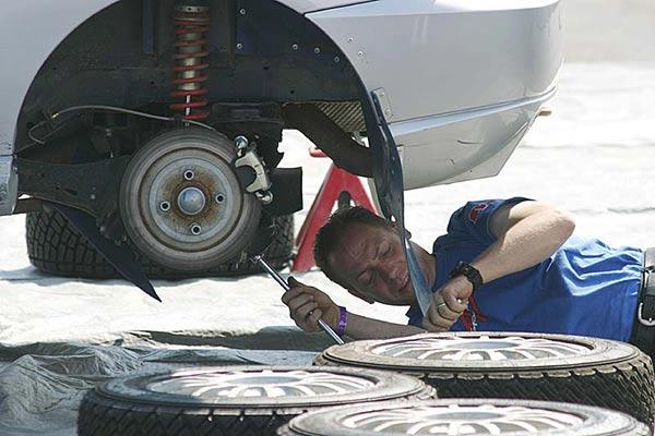 An auto mechanic working on a rally car. (Photo courtesy Wikimedia Commons)