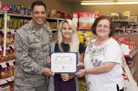 Katie Vosler, center, accepts a $2,000 college scholarship from Col. Dwayne LaHaye, left, the 71st Mission Support Group commander, and Sheila Gilbert, the director of the Vance Air Force Base Commissary, during a brief ceremony at the Commissary.  (U.S. Air Force/James Bolinger)