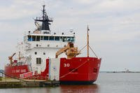 U.S. Coast Guard Cutter Mackinaw moors in Cleveland harbor, July 12, 2017. The Cleveland Harbor West Pierhead Lighthouse is visible in the background, west of Mackinaw. (US Coast Guard/Brian McCrum)