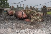 Pfc. Michael Williams, Company A, 2nd Battalion, 10th Infantry Regiment, low crawls under a barbed-wire obstacle at the confidence course as part of a six-week Basic Combat Training cycle for prior-service Soldiers. Williams, who served in the U.S. Navy from 2008 to 2014, is one of 32 prior-service Soldiers conducting training with Co. A. (Stephen Standifird/U.S. Army)