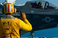 Aviation Boatswain's Mate (Handling) 2nd Class James Spencer signals the pilot of an F-35B Lightning II aircraft with Marine Fighter Attack Squadron (VMFA) 121 on the flight deck aboard the amphibious assault ship USS Wasp (LHD 1). (U.S. Navy/Mass Communication Specialist 2nd Class Michael Molina)