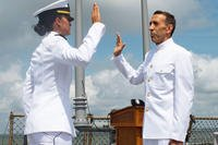 Dr. Tyrone Krause recites the commissioning oath given by his daughter, Ensign Laura Krause, the Assistant Chief Engineer aboard the Arleigh Burke-class guided missile destroyer USS Ramage (DDG 61), during a commissioning ceremony aboard the ship, July 13, 2018. Krause was inspired to join the Navy shortly after his daughter's commissioning in 2015. (U.S. Navy photo/Maxwell Anderson)