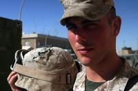 Lance Cpl. Bradley A. Snipes stands with the helmet that saved his life. During a mission with his platoon, Snipes was shot in the head by an enemy sniper. The only thing that saved his life was the Kevlar helmet he wore. (U.S. Marine Corps/Sgt. Jerad W. Alexander)