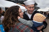 Electrician's Mate 3rd Class Eric Sacc, assigned to the Nimitz-class aircraft carrier USS Harry S. Truman (CVN 75), hugs his wife and son upon the ship's return to homeport, Dec. 16, 2018. (U.S. Navy photo/Jessica L. Dowell)