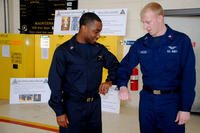 Operations Specialist 2nd Class Martin Vories compares the flame-resistant variant coverall with a standard coverall worn by Aviation Machinist's Mate 2nd Class Mark Birzer. (US Navy photo)