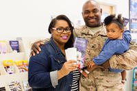 An Army soldier with his wife and daughter looking at vacation brochures (Photo: U.S. Army MWR)
