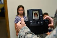 An Air Force child gets her passport photo taken at Dover Air Force Base, Delaware. (U.S. Air Force photo/Airman 1st Class William Johnson)
