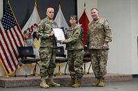 Command Sgt. Maj. Mark Bowman, the State Command Sergeant Major, Illinois National Guard presents a certificate of promotion to Sgt. Maj. Sharon Hultquist of Delavan, Illinois. (U.S. Army National Guard/SSgt Robert R. Adams)