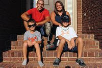 Staff Sgt. Rey Edenfield poses with his wife, Amy, and their two sons, Grayson, left, and Dawson on the front porch of their home. Edenfield is an air traffic controller at Maxwell Air Force Base, Alabama. (U.S. Air Force /Staff Sgt. Erica Picariell)