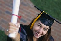 A recent graduate holds a degree and smiles.
