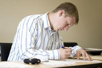 Man writing at a desk wearing a collared shirt.