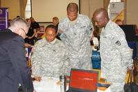 Non-commissioned officers receive information from an employer at a U.S. Army Garrison Rock Island Arsenal Employment and Education Event