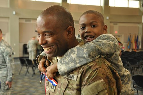 Georgia Army National Guard Capt. Chad Tyson receives a hug from son Chase during a welcome home ceremony for the Georgia National Guard's Agribusiness Development Team III in Marietta, Georgia. (National Guard/William Carraway)