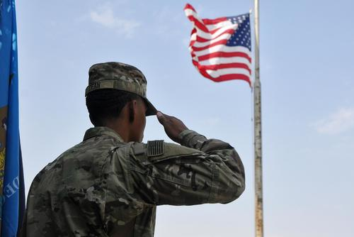 A soldier salutes the U.S. flag during the singing of the National Anthem on Sept. 11, 2017, at Camp Arifjan, Kuwait. (U.S. Army photo by Sgt. Kimberly Browne)